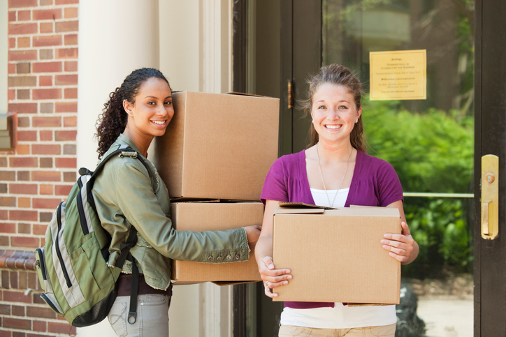 Subject: Two University students in front of their dorm moving boxes in a college campus.
