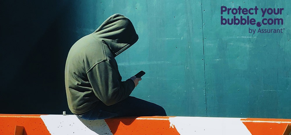 Man sitting on a barrier with a mobile phone in a hoodie