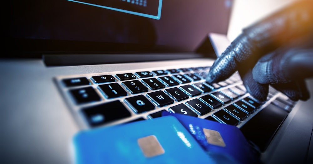 Picture of gloved hand and credit card on laptop